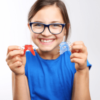 Preteen girl holding up orthodontic appliances