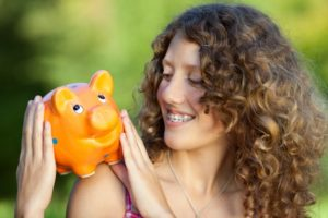 Woman with braces in Hopkinton holding piggy bank and smiling